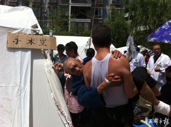 A man holds his father, injured in the earthquake, while they wait for him to have surgery. Photo: China Christian Council