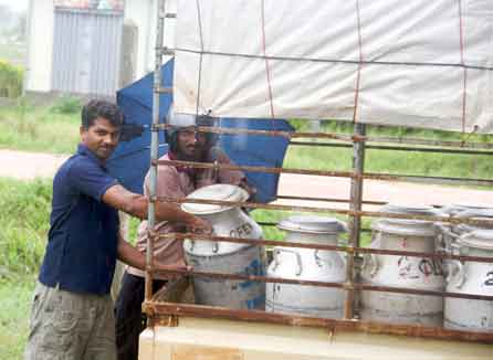 An OfERR staff members helps load milk collected by returned refugees onto a truck.  Photo: Simon Chambers