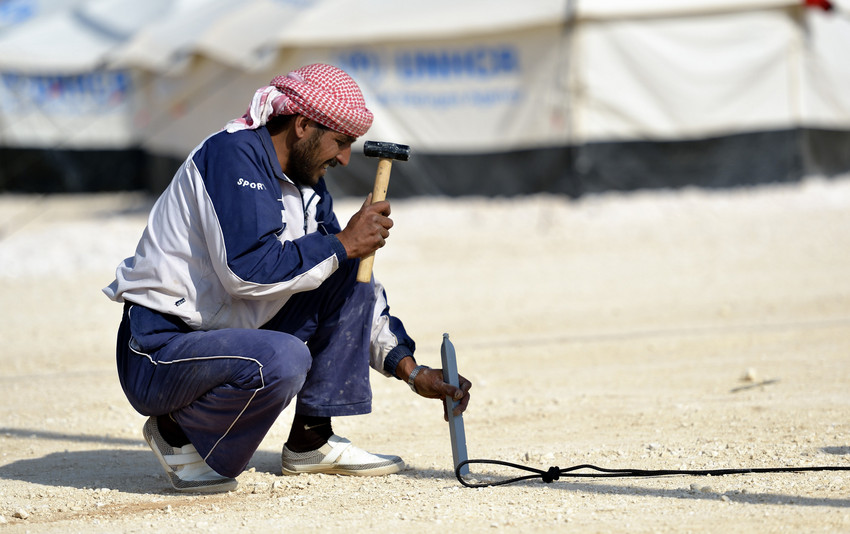 A worker pounds a peg into the ground as he and other workers erect new tents in the Zaatari Refugee Camp, located near Mafraq, Jordan. Opened in July, 2012, the camp is now the second largest refugee camp in the world. Members of the ACT Alliance are active in the camp providing essential items and services. Photo: Paul Jeffrey/ACT