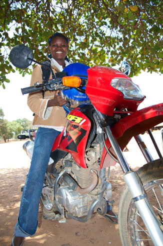 Lucia Simba and her motorcycle visit remote communities on behalf of EHALE, a PWRDF partner in Mozambique, bringing health information and care.  Photo: Simon chambers