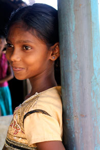 Sri Lankan girl, a former internally displaced person, smiles from the doorway of her new home in northern Sri Lanka. Photo: Carolyn Vanderlip
