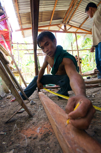 Exposito Guimalan, a professional carpenter supervising construction of houses after the Bohol earthquake, measures before making a cut. Photo: Simon Chambers