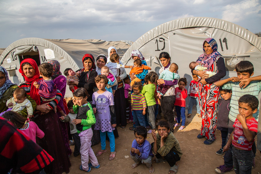 Syrian refugees in local refugee camp in Suruc, Turkey - mothers with small chlidren standing in line in front of medical tent. Photo: Mike Kollöffel/ACT