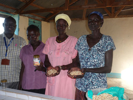 Ana Daborah (right) and other refugees, along with a staff member from the NCCK, show some of the supplies for their peanut butter business in the Kakuma refugee camp. Photo: Jeannethe Lara
