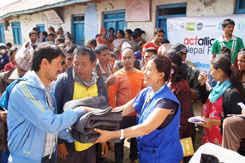 LWF Nepal project coordinator Nibha Shresta hands out blankets to earthquake survivors in Ghuse. Photo: ACT/LWF/C. Kästner