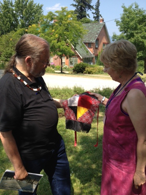 Joy Gothard presents Bishop Mark MacDonald with a prayer flag representing the Four Directions