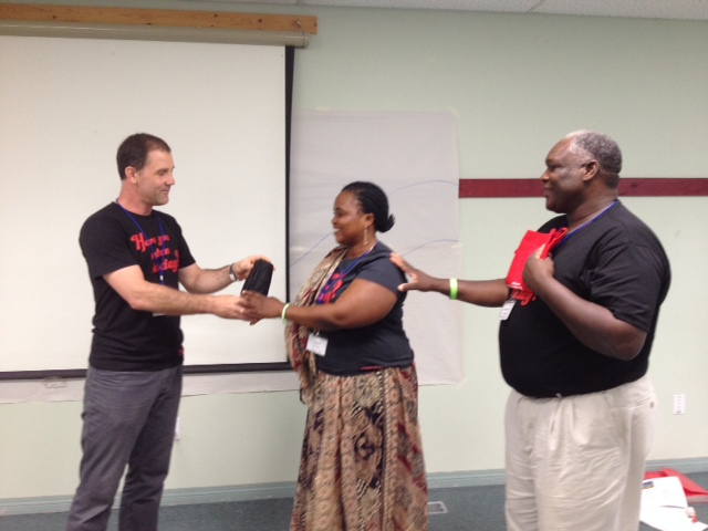 James Kornelson presents Joyce Berno Mtauka and Geoffrey Monjesa of Tanzania with gifts from the Canadian Foodgrains Bank.