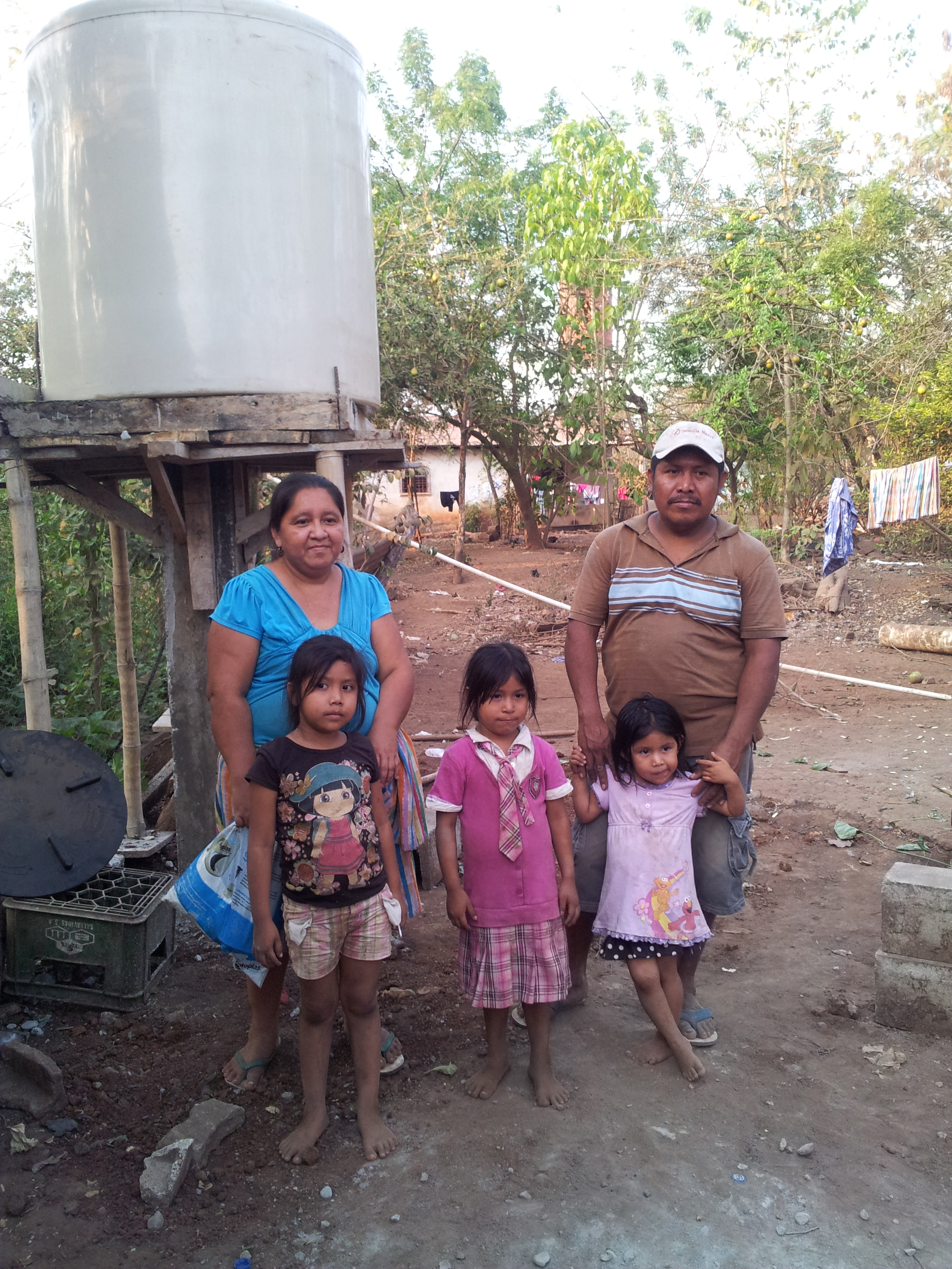 Irma Gonon and her family use the water storage system behind them to irrigate their crops and provide water for their home. Photo: Elsa Tesfay