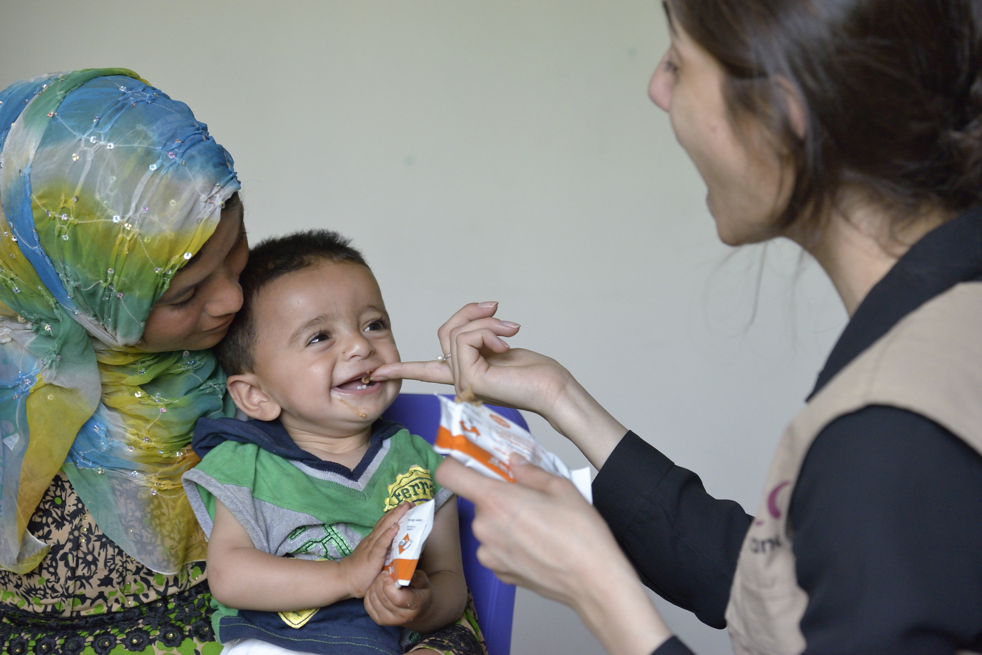 Maha Haidar, a health and nutrition specialist with International Orthodox Christian Charities, a member of the ACT Alliance, feeds 11-month old Abdul as his mother, Rokaya Al Ali, holds him in the community health center in Kab Elias, a town in Lebanon's Bekaa Valley which has filled with Syrian refugees. Photo: Paul Jeffrey/ACT