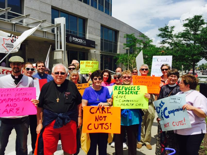 Clergy and lay people from the Diocese of Niagara protest the cuts to refugee health care at a rally organized in June 2015 in Hamilton. Photo: Diocese of Niagara