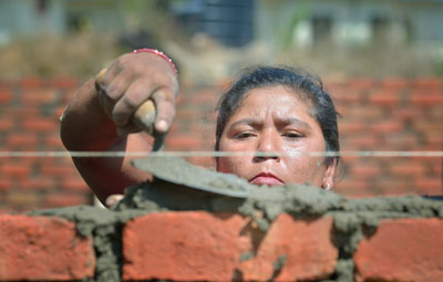 Bhagwati Tamang lays bricks in Jogimara, a village in the Dhading District of Nepal Tamang, an experienced mason, has helped the ACT Alliance train other carpenters and masons in the community so they'll be ready to help construct permanent housing. Photo: ACT/Paul Jeffrey