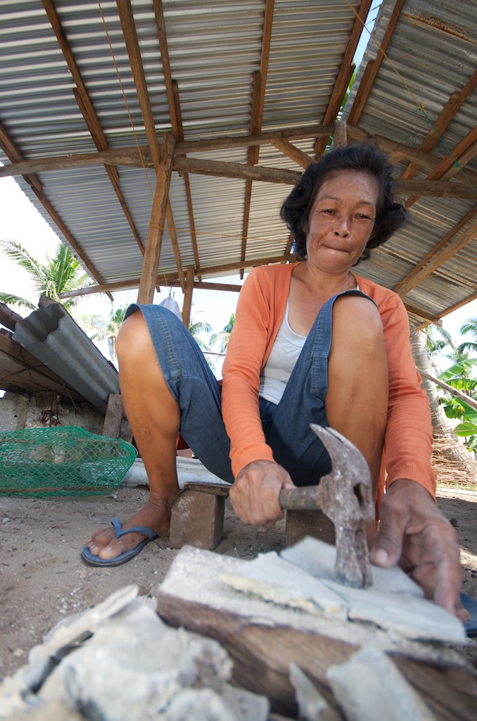 Emelda Chavez breaks up concrete from her original house, which was destroyed during Typhoon Haiyan, to use as flooring material in the new home she and members of the Kaongkod Fishermen's & Farmer's Association are helping to build with supplies provided by PWRDF partner FARDEC.