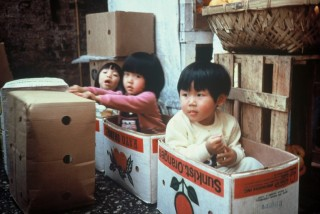 "The children of migrant workers take ""alternative transport"" in a Hong Kong market. Photo: Phil MacIntyre-Paul, 1984"