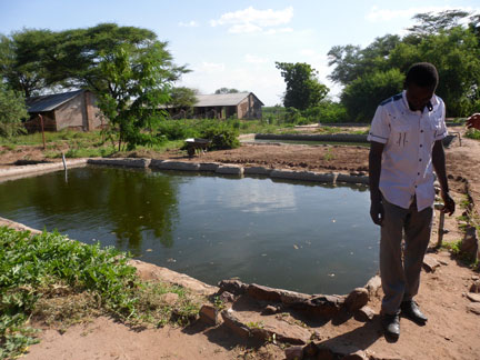 Noah Errambona, a Burundian refugee at the Kakuma refugee camp in Kenya, at the fish pond he and some fellow refugees are using for income.  Photo: Jeannethe Lara