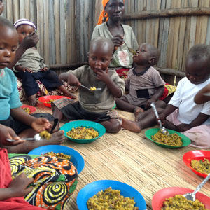Young children in Burundi eating a meal prepared by their mothers, who are part of a nutrition course provided by the Diocese of Bujumbura, a PWRDF partner. Photo: Zaida Bastos