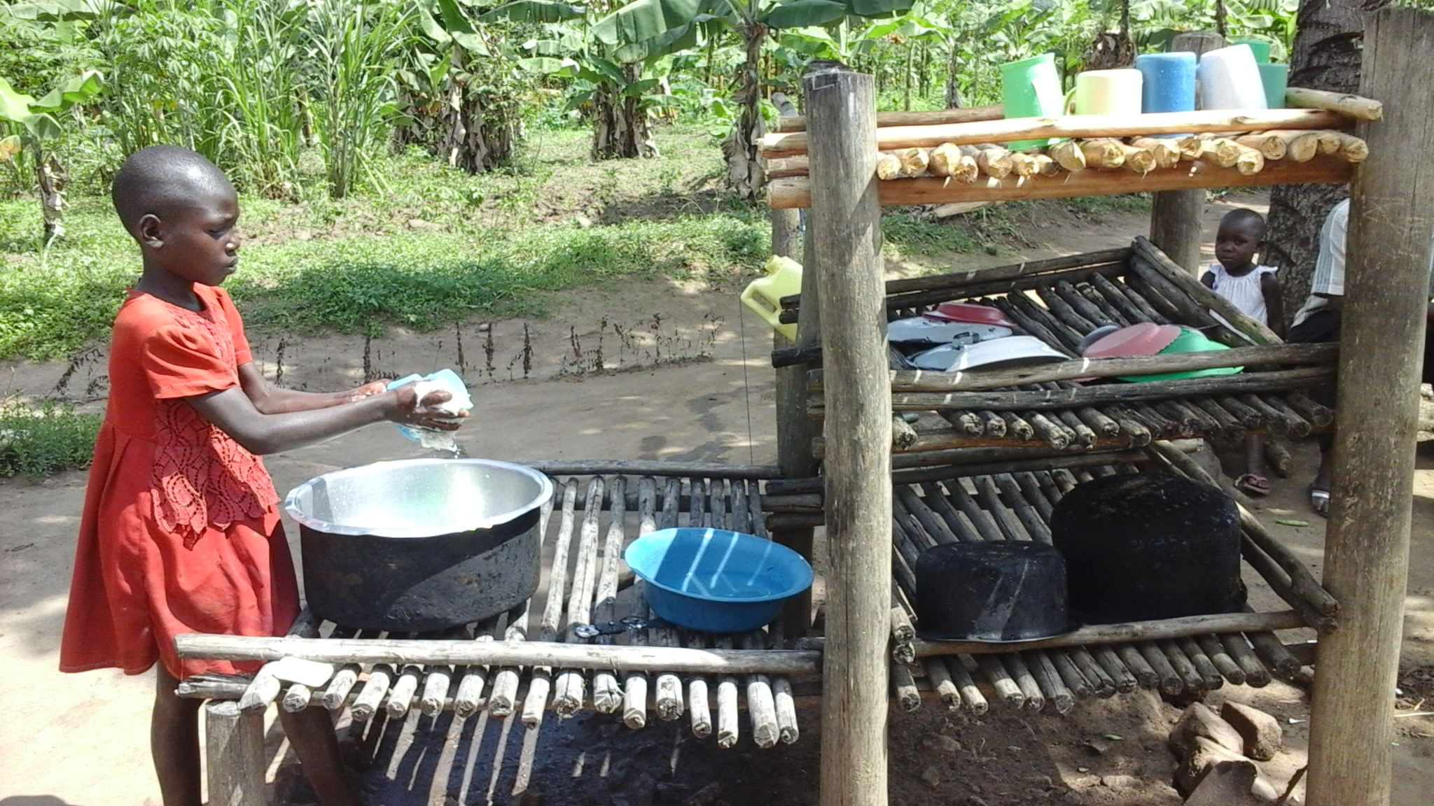 A beneficiary washes dishes using an improved dish rack.
