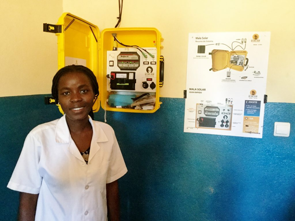 A nurse stands in front of newly installed Solar Suitcase